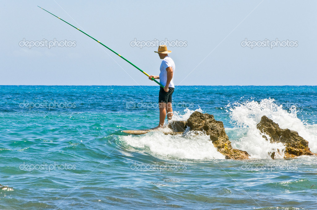 The fisherman in a vest and a hat fishing on stones in sea waves — Stock Photo #1088229