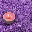 Heap of violet bath salt wiih candle - Stock Photo