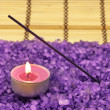 Heap of violet bath salt with candle - Stock Photo
