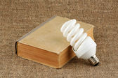 The power saving up bulb and the book — Stock Photo