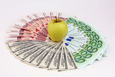 Yellow apple and denominations — Stock Photo