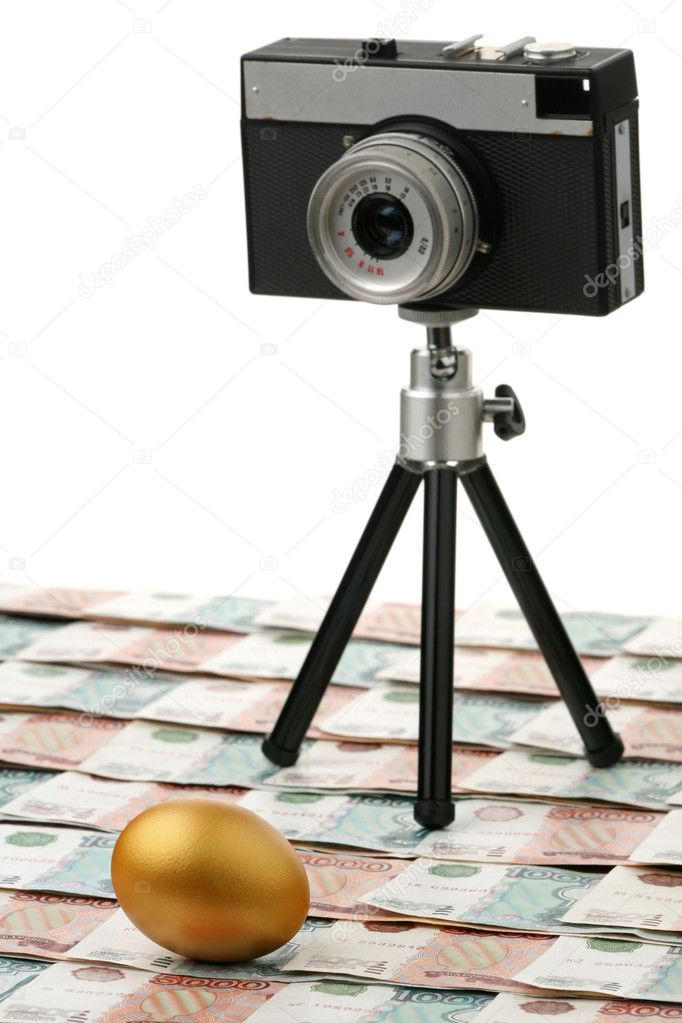 The camera and gold egg against money — Stock Photo #1514537