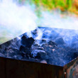 Hot coals with smoke — Stock Photo