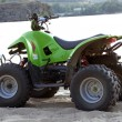 Small All Terrain Vehicle on coast of th - Stock Photo