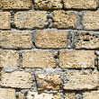 Wall from a rough yellow brick. backgrou — Stock Photo
