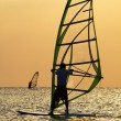 Silhouettes of a windsurfers on waves of — Stock Photo