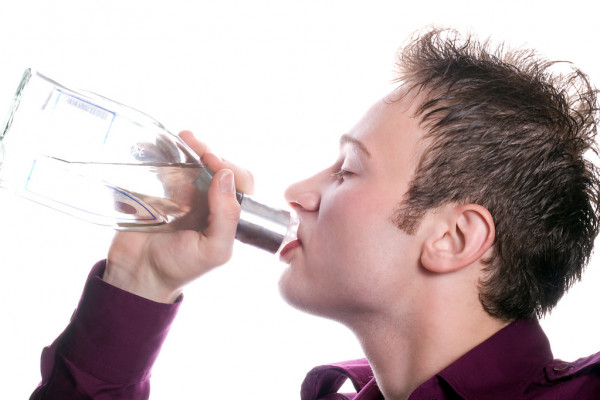 The young man drinks vodka from a bottle — Stock Photo © Sergey ...