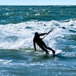Silhouette of a kitesurfer on waves of a — Stock Photo