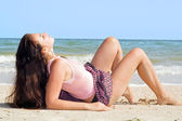 The beauty young woman lies on sand at s — Stock Photo