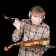 The young man in ear-phones eats a violi — Stock Photo