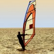 Silhouette of a windsurfer on waves of a — Stock Photo