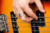 Hand of the guitarist on guitar strings — Stock Photo