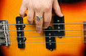 Hand of the artist on guitar strings — Stock Photo