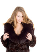 The young beautiful woman in a fur coat — Stock Photo