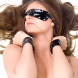 Sexy young woman in handcuffs and a band — Stock Photo
