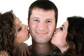 Two beautiful girls kiss the young man — Stock Photo