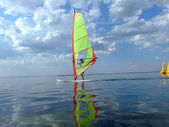 Windsurfer and its reflection in water o — 图库照片