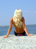 The girl-blonde sits on coast of a gulf — Stock Photo