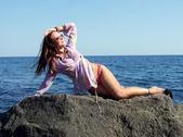 A garota sexual coloca sobre uma rocha e parece — Foto Stock