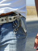 The handcuffs hanging on a belt of jeans — Stock Photo
