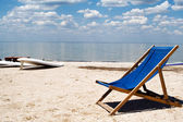 Chair on a beach against a gulf and clou — Stock Photo