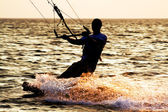 Silhouette of a kitesurfer on a waves — Stock Photo
