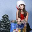 Girl with purchases in Christmas cap — Stock Photo #1233128