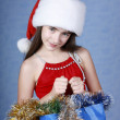 Girl with purchases in Christmas cap — Stock Photo #1233251
