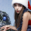 Surprised girl in a Christmas cap - Stock Photo