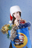 Girl with purchases in the Christmas cap — Stock Photo