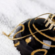 Black Christmas bauble on to snow. - Stock Photo