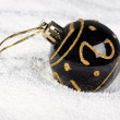 Black Christmas bauble on to snow. - Foto de Stock