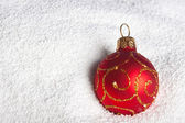 Red Christmas bauble on to snow. — Stock Photo
