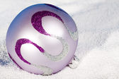 Tender lilac Christmas bauble on to snow — Stock Photo