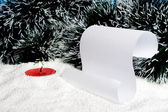 Burning candle and scroll on snow. — Stock Photo