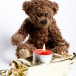 Toy bear Teddy and burning candle. — Stock Photo