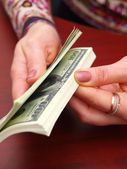 Female hands recalculate a pack of dolla — Stock Photo