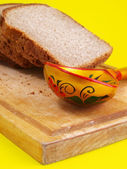 Bread, spoon and board on a back — Stock Photo