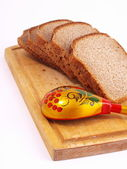 Bread, spoon and board on a white — Stock Photo