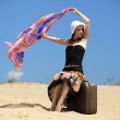 Suitcase standing on the sand beach and girl is — Stock Photo