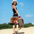 Beautiful girl is walking on a sand with a suitc — Stock Photo #1390753