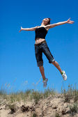 Girl jumping on a background of blue sky — Stock Photo
