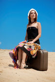 Girl and suitcase on the sand beach — Stockfoto