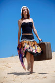 Beautiful girl is walking on a sand with a suitc — Stock Photo