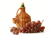 Red grape with wicker wine bottle — Stock Photo