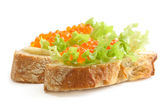 Sandwiches with red caviar and green sal — Stock Photo
