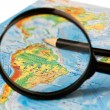 Magnifying glass and a pencil on the background maps — Stock Photo #1797957