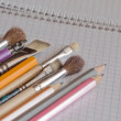 Pencils and brushes on copy-book — Stock Photo #1100476
