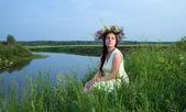 Pretty girl in flower chaplet against r — Stock Photo