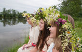 Three girls in flower chaplet — Stock fotografie